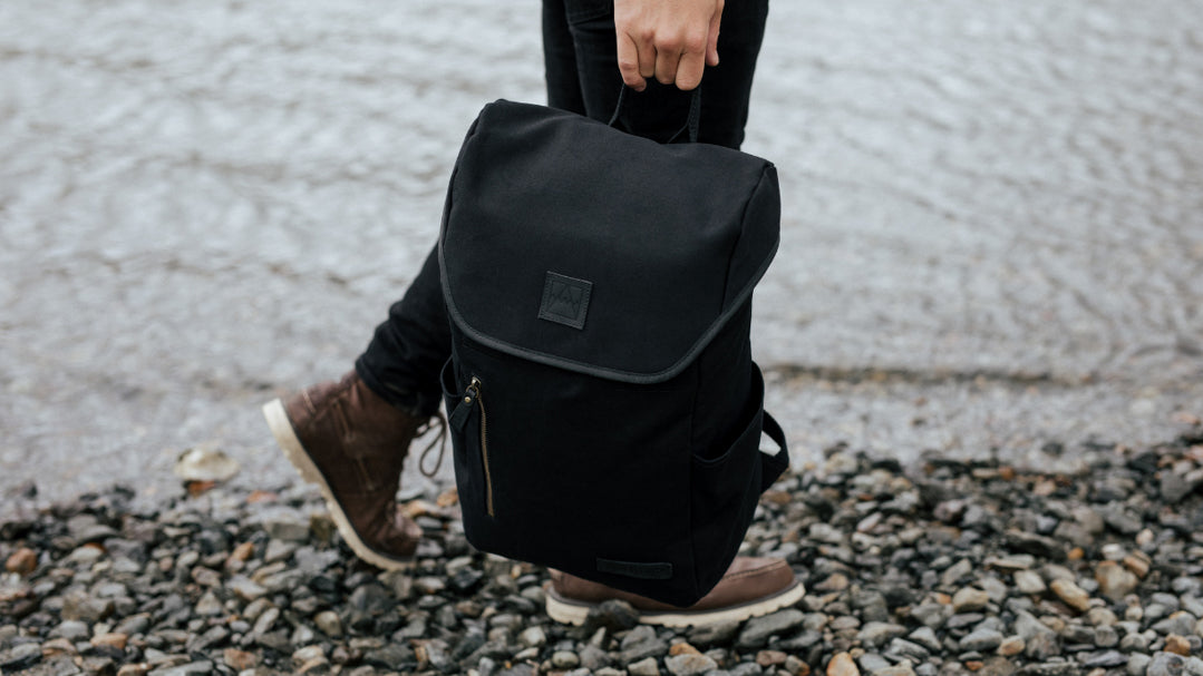 All Black backpack next to sea