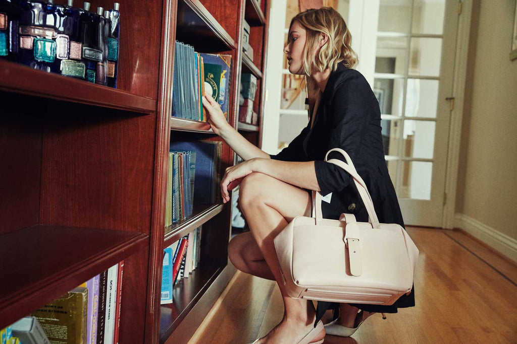 Model holding Doctor Bag in Blush while browsing through books