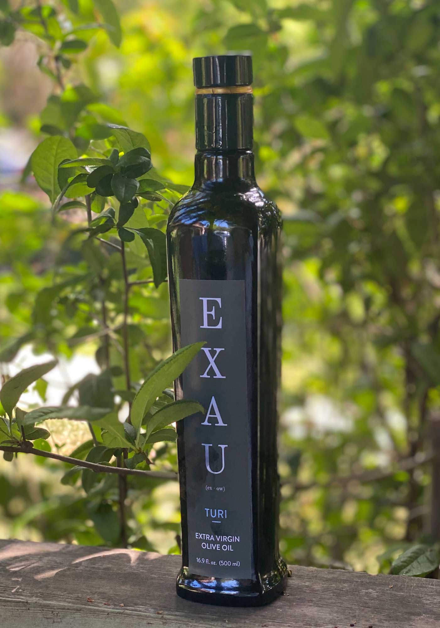EXAU bottle in front of trees