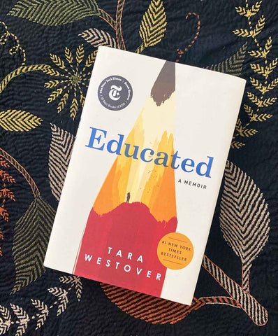 Educated by Tara Westover against a patterned throw