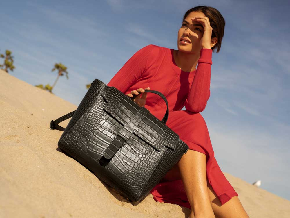 Woman with Black Handbag on Beach