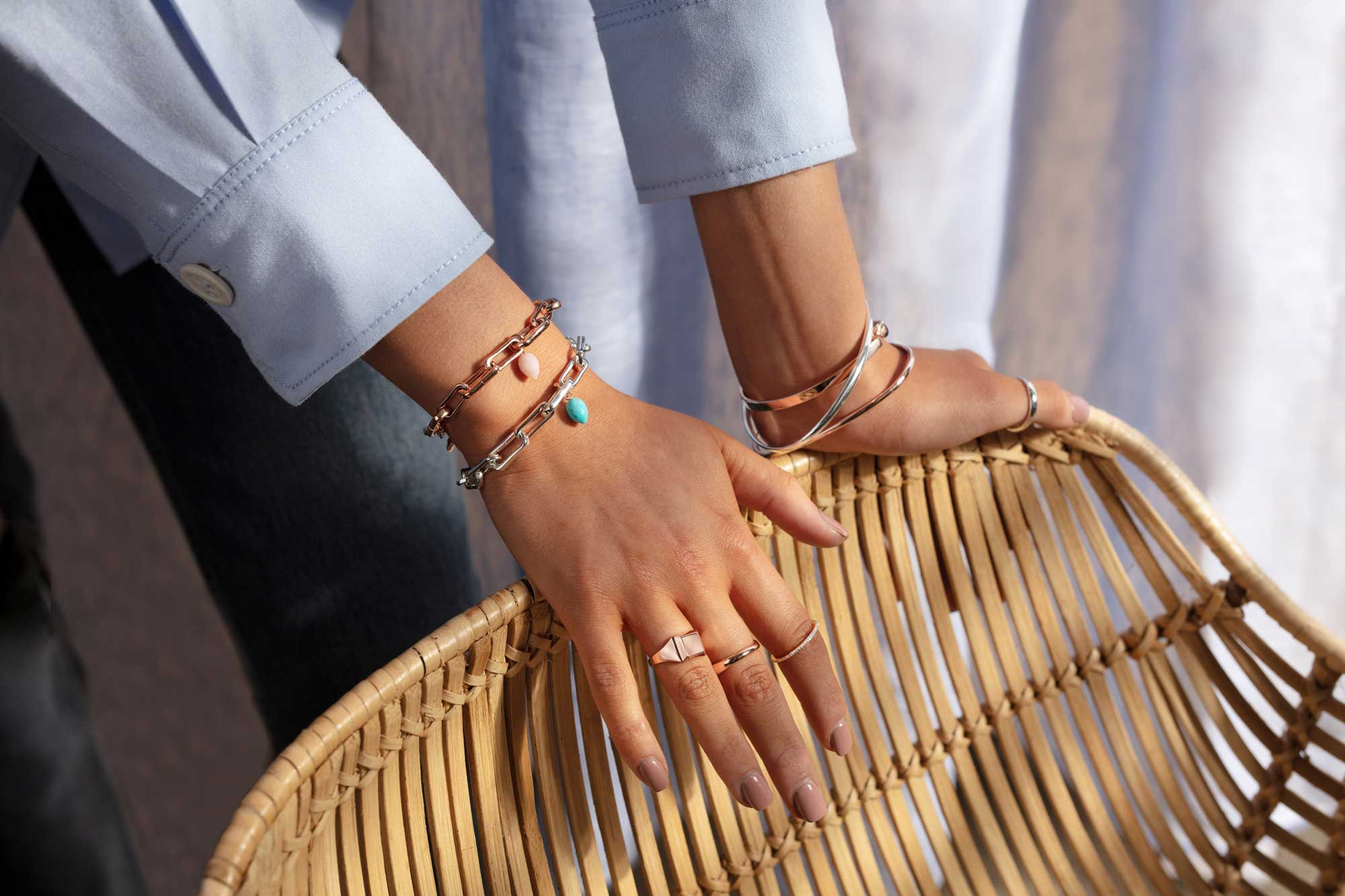 Hands over chair with Monica Vinader rings and bracelets