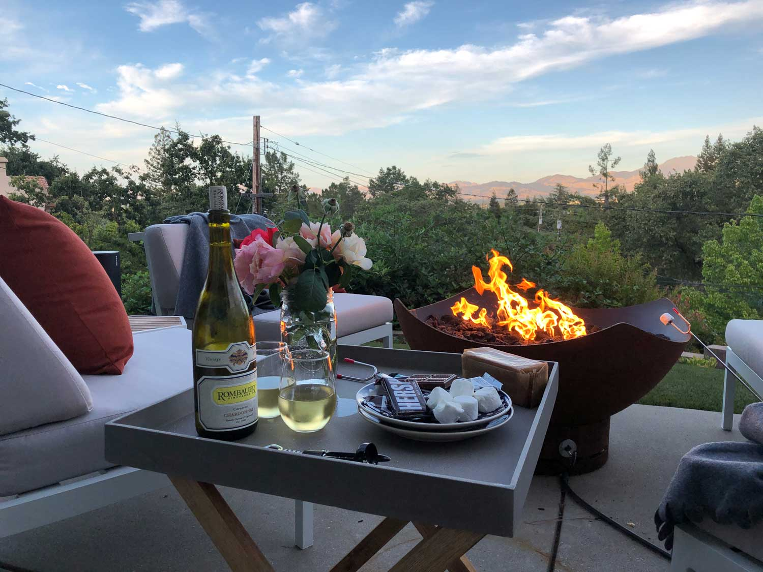 View of firepit, s'mores and wine glasses