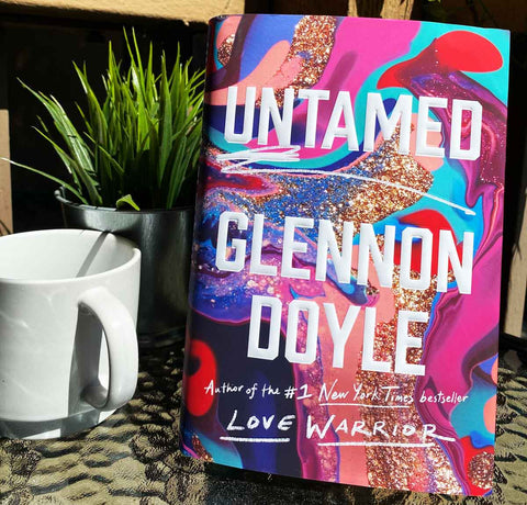Untamed next to a coffee cup and plant in the background