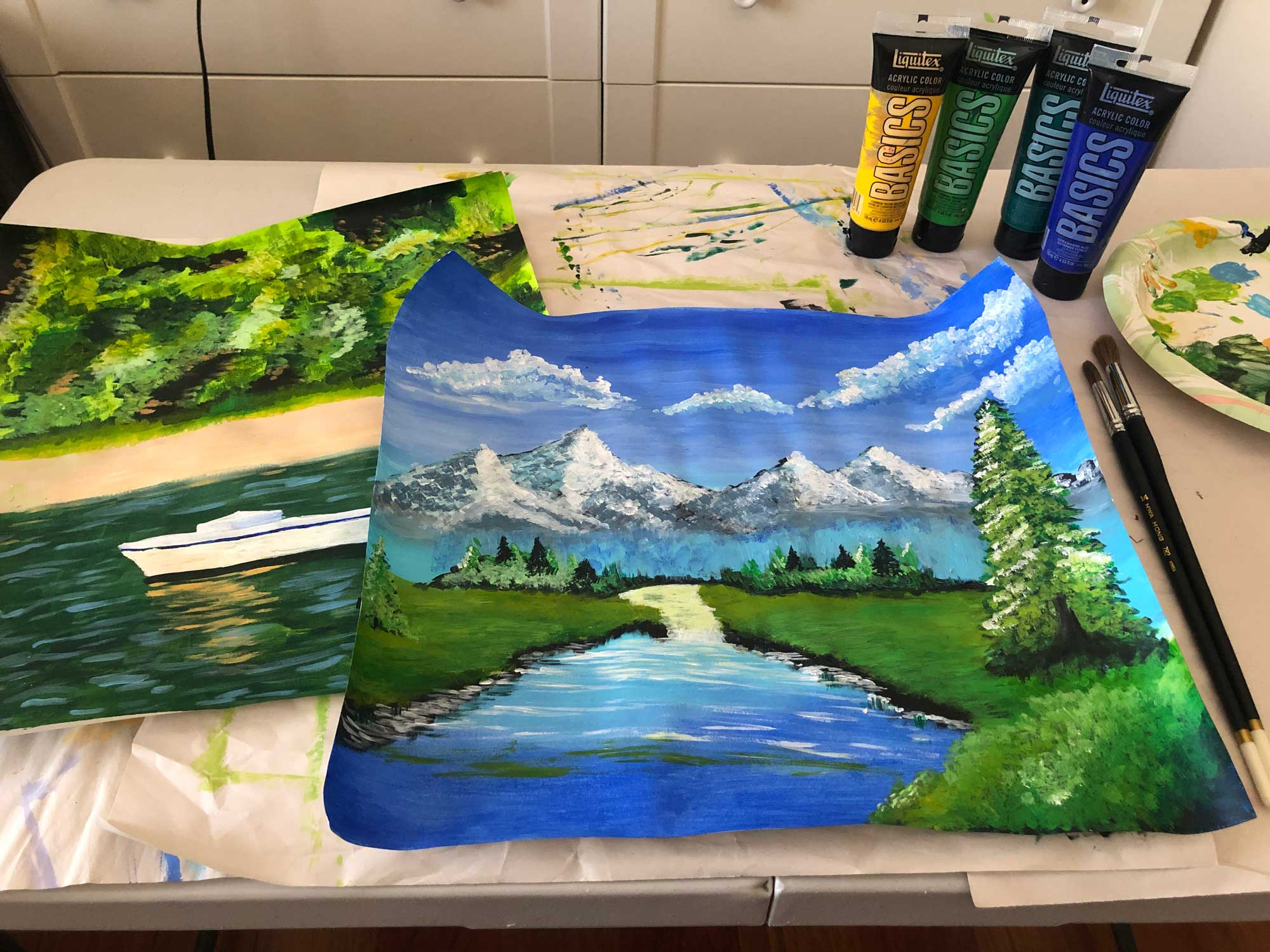 Acrylic paints next to painting of landscape