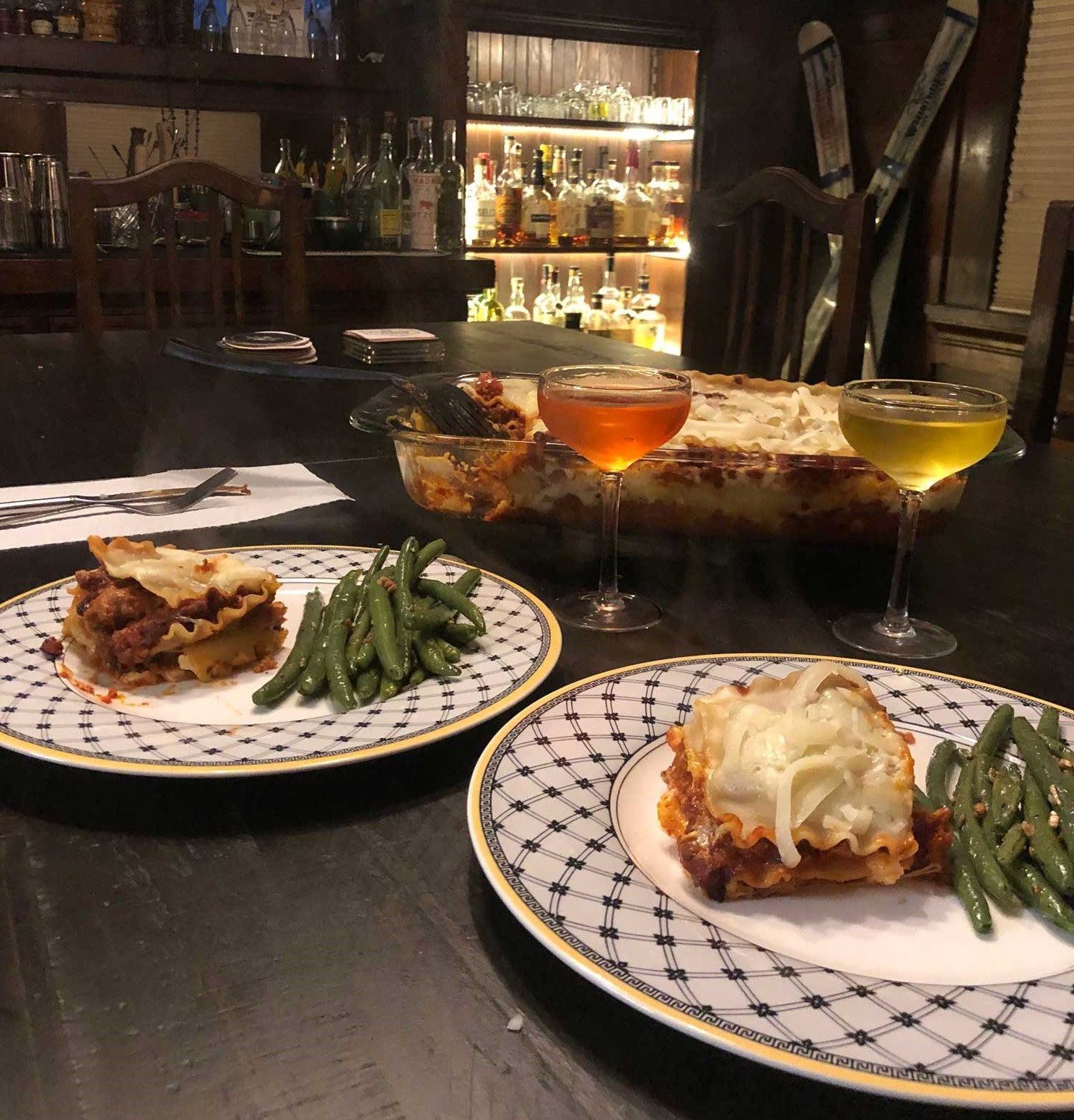 Plate of lasagna and green beans, in front of coupe glasses