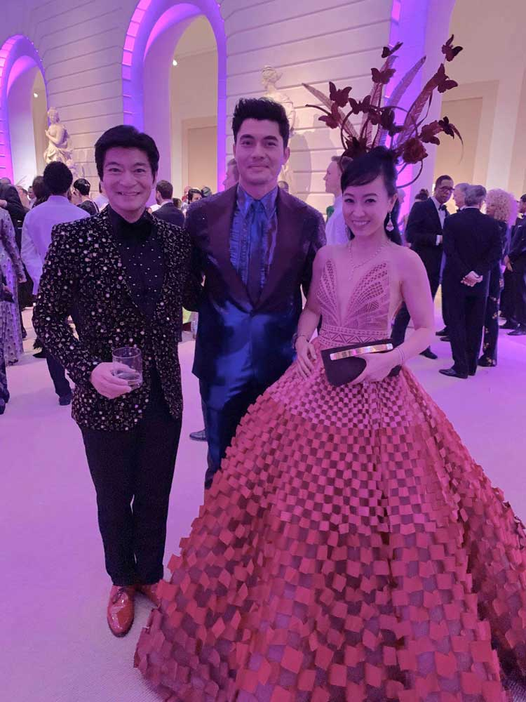 Coral and husband posing with Henry Golding