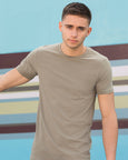 Man with short brown hair modelling a plain light-stone coloured t-shirt that you can personalise with custom print