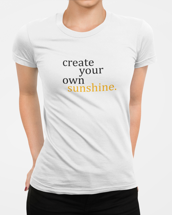 Woman wearing a white t-shirt with a slogan stating Create Your Own Sunshine