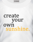 White t-shirt with a slogan stating Create Your Own Sunshine