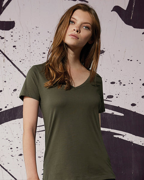 Woman with long brown hair modelling a plain green organic t-shirt that you can personalise
