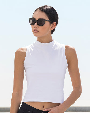 Stylish woman with black hair and sunglasses modelling a white high neck crop top that can be personalised