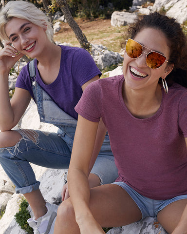 Two women smiling modelling a plain burgundy t-shirt and a plain purple t-shirt that you can personalise with custom design