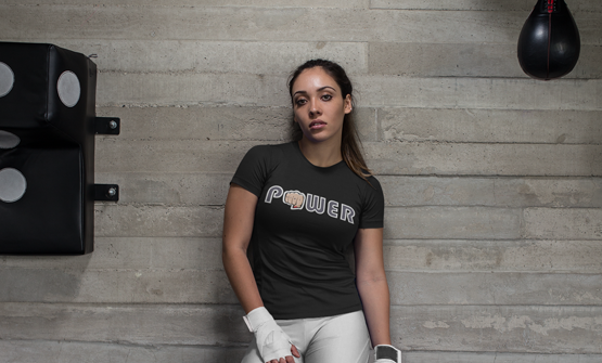 Woman standing against a wall in a gym wearing a custom t-shirt with a personalised t-shirt design which says girl power