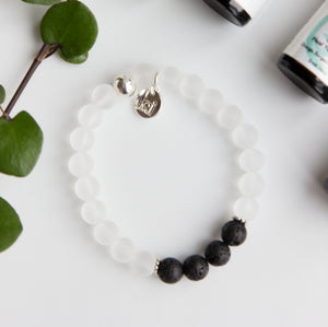 Beautiful 8mm matte clear quartz semi-precious stone blessing bracelet featuring 4 lava stones and your choice of essential oils for love, protection, grounding and/or grief; adorned with sterling silver ball bead and charm, stretch, measures 18.4 cm