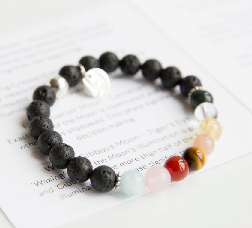 Beautiful lava stone bracelet is adorned with 8 unique semi-precious stones representing each phase of the Moon's cycle. Use your bracelet and essential oil to connect to the Moon's phases and harness its energy in your spiritual practice. Adorned with sterling silver ball bead and charm, stretch, measures 18.4 cm.