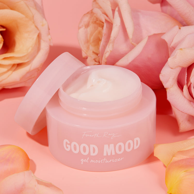 Good Mood gel moisturizer , with an open lid ; in front of pink roses