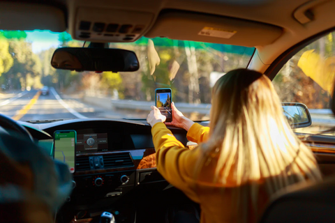 Alt text: A woman takes a video of a road trip for TikTok.