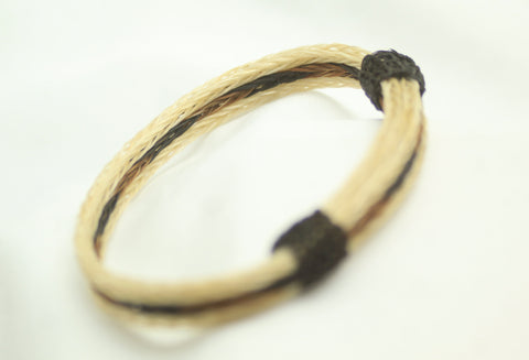 adjustable horsehair bracelet.  3/8 inches wide. white border with black and brown braided center. black knots
