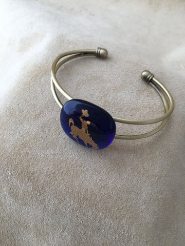 Adjustable bracelet with a blue fused gall focal piece with 22kt gold university of Wyoming Bucking bronco and rider
