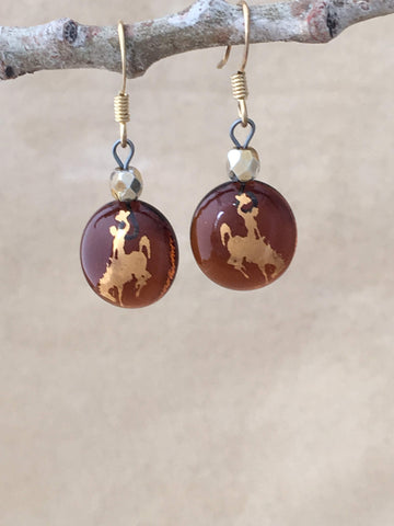 University of Wyoming Cowboy Round Dangle Earrings of rootbeer colored fused glass, 22kt gold foil bucking bronco and rider, ear wires