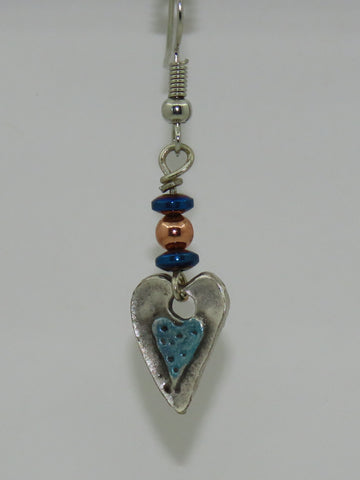 "Blue Sliver Heart Earrings Artist: Jackie Olaveson, Metalsmith Hand pounded silver with hand painted blue heart center   11/2"" Long x  1/2"" Wide  Two blue bead discs with smaller copper bead accent  Stainless steel ear wires  Would look great with a blazer with jeans or elegant outfit for out on the town  Please note, each jewelry piece is custom designed by the Artist , with a slight variation between each piece"
