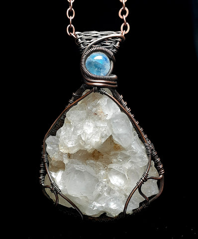 unique harlequin quartz cluster wrapped in copper wire with rainbow moonstone accent. brown leather cord with lobster clasp