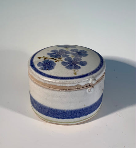 "Blue Flower / Stripe White Round Box Muffy Moore: Ceramic Potter White round box with blue flowers on lid with stipes  Round stoneware lid  4"" Long  x  4"" Wide x 3"" Tall  Beautiful hand thrown stoneware round box Dishwasher, oven and food safe  Great for kitchen storage  Please note Items are handmade by Artist and there is a slight variation from piece to piece"