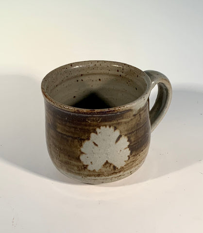 "Grey / Brown Leaf Stoneware Mug Muffy Moore: Ceramic Potter Grey and Brown  with Leaf decoration on mug Nice size handle and good size mug overall   3.5"" Long  x 3.5"" Wide x 4"" Tall  Beautiful hand thrown stoneware mug  Dishwasher, oven and food safe  Great for kitchen storage  Please note Items are handmade by Artist and there is a slight variation from piece to piece"