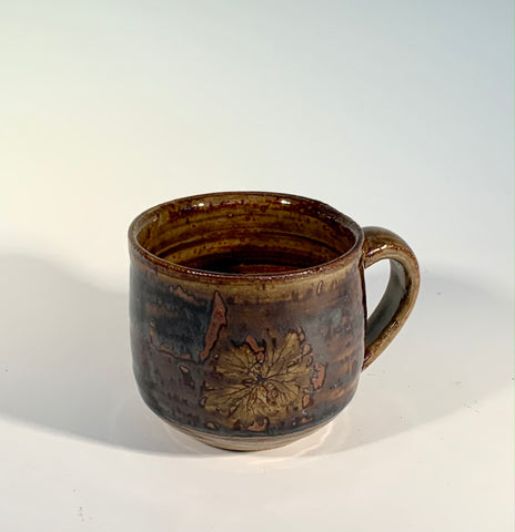"Tan /Brown Leaf Stoneware Mug Muffy Moore: Ceramic Potter Tan with dark brown accents  Nice size handle/ good size mug overall with tan / brown tones with leaf decoration  3"" Long  x 3"" Wide x 3"" Tall  Beautiful hand thrown stoneware mug  Dishwasher, oven and food safe  Great for kitchen storage  Please note Items are handmade by Artist and there is a slight variation from piece to piece"