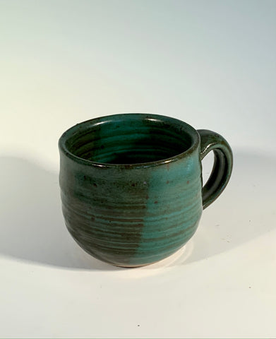 "Opaque Green Glaze Stoneware Mug Muffy Moore: Ceramic Potter Green with dark green accents  Nice size handle/ good size mug overall with light green and dark green accents  3.5"" Long  x 3.5"" Wide x 3.5"" Tall  Beautiful hand thrown stoneware mug  Dishwasher, oven and food safe  Great for kitchen storage  Please note Items are handmade by Artist and there is a slight variation from piece to piece"