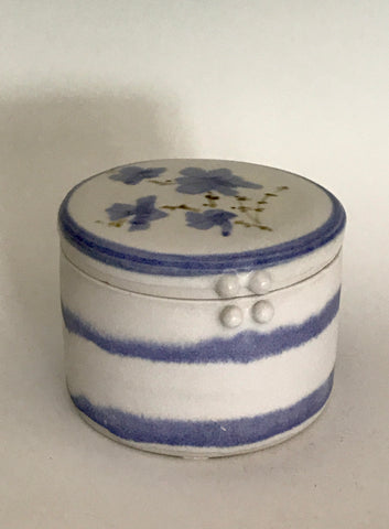 "White / Blue Striped / Flower Porcelain Round Box Muffy Moore: Ceramic Potter White and blue striped with flower porcelain round box  White with blue strip and blue flower accents   4"" Long  x 4"" Wide x 3"" Deep  Dishwasher safe  Great for jewelry and other what nots   Please note Items are handmade by Artist and there is a slight variation from piece to piece"