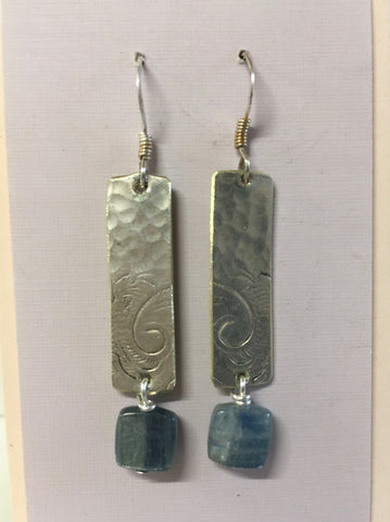 "Embossed Silver Plate Rectangles With Kyanite Square Earrings Artist: Terry Kreuzer  Rectangle Embossed Silver Plate with 1/4"" square Kyanite Stone at the bottom  1 1/4"" Long x 1/4"" wide  Stirling Silver ear wires  Please note, the jewelry is custom designed by the Artist , with a slight variation between each piece"