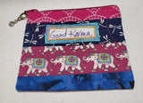 "Good Karma Zipped Coin Purse Glenda Haley, Fabric/woodworker Artist Coin Purse is 5"" x 1/8"" x 3 3/4"" Coin Purse has elephants/dragonfly pattern Coin purse zips Coin purse is cotton fiber Hand Wash Please note, the coin purses are a custom designed by the Artist , with a slight variation between each piece"