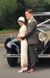 The bride and groom wearing their 1920s outfits, bride in Anna Chocola cloche hat