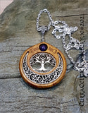 Oval Tree of Life symbol mounted in Iroko hardwood and embellished with an Amethyst bead.