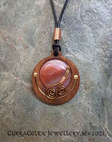Cabochon of Cherry Quartz mounted in an Iroko textured wood bezel and decorated with bronze spirals and bright copper accents.