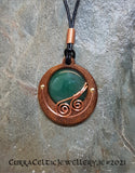 Cabochon of Green Aventurine mounted in an Iroko textured wood bezel and decorated with bright copper spirals.