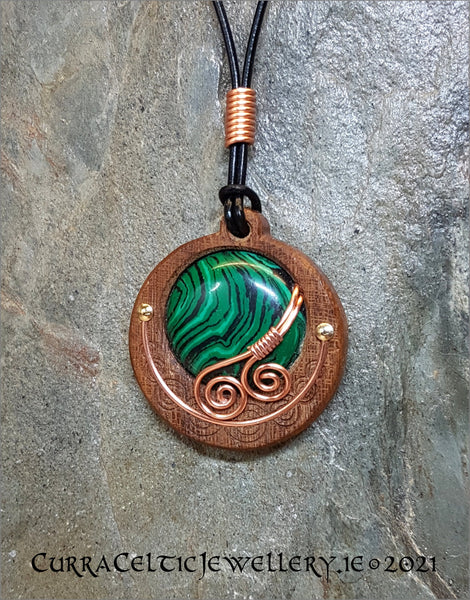Cabochon of Malachite mounted in an Iroko textured wood bezel and decorated with bright copper spirals.
