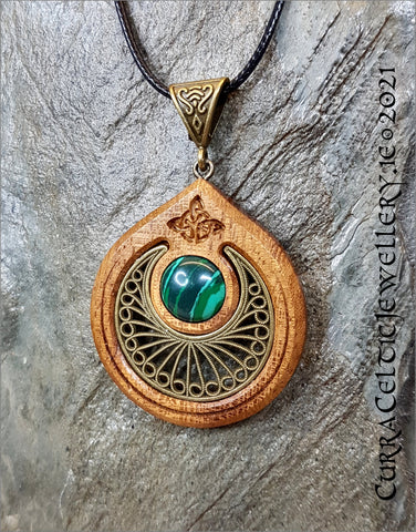 Featuring a fine bronze filigree scallop with a cabochon of Malachite mounted in an Iroko hardwood bezel.