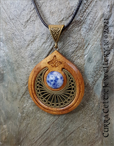 Featuring a fine bronze filigree scallop with a cabochon of Sodalite mounted in an Iroko hardwood bezel.