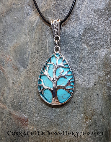 Turquoise gemstone mounted in a Tree of Life chrome bezel with Celtic weave bail.