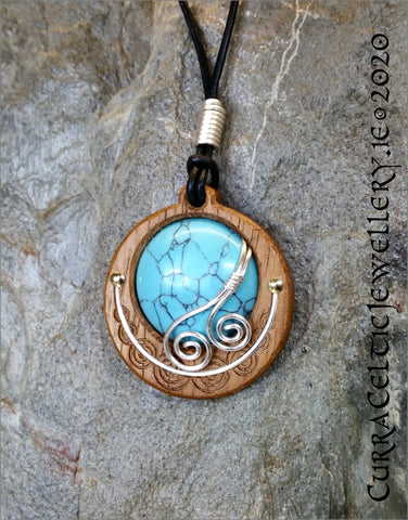 Cabochon of Turquoise mounted in an Iroko textured wood bezel and decorated with some with bright silver wire spirals.