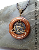 Bronze Triquetra on Iroko hardwood with gold wire accents and bronze bail.
