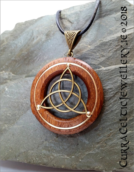 Bronze Triquetra on black Walnut with gold wire accents and bronze bail.