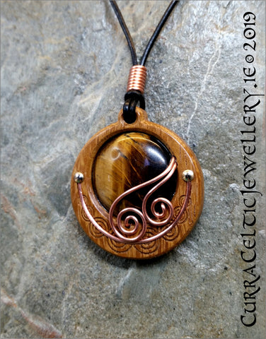 Cabochon of nicely marked Tiger's Eye mounted in an Iroko textured wood bezel and decorated with some with bright copper wire spirals.