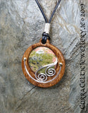 Cabochon of Unakite mounted in an Iroko textured wood bezel and decorated with some with bright silver wire spirals.