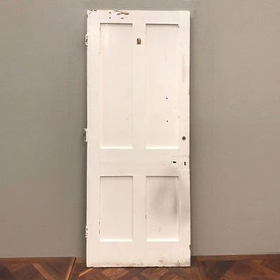 A reclaimed victorian internal door with four simple recessed panels in solid pine, painted white.