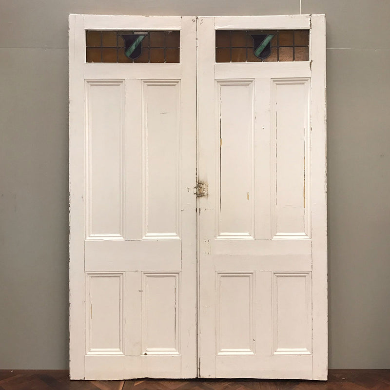 A pair of Edwardian dividing doors in pine. These attractive reclaimed doors feature a recessed five panel design with a stained glass window. An interesting shield design in blue and orange.  These doors are being sold in their current painted state