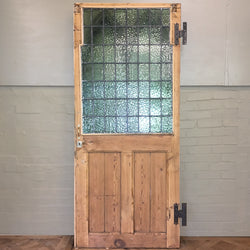 This reclaimed Gothic Revival style  door dated from the early 1900's features two ornately framed lead lined windows on the front and a large unframed panel on the reverse